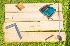 Wooden planks and fret saw. On green grass Stock Photography
