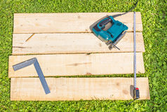 Wooden planks and fret sew. Wooden planks and fret saw on green grass Royalty Free Stock Photo