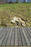 Wooden planks, grass and rocks in the background Royalty Free Stock Images