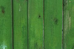 Wooden planks of green color on the fence as an abstract background. Old paint, board royalty free stock photography
