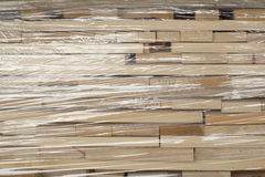 Wooden planks stacked in rows wrapped in plastic foil Royalty Free Stock Photos