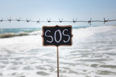 Wooden plaque in the inscription sos. On the background of the sea with barbed wire Royalty Free Stock Image