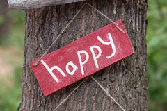 A wooden plaque with the word happy royalty free stock image