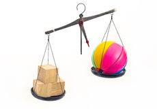 Wooden and plastic toys symbolically weighed on the scales. Royalty Free Stock Images