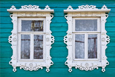 Wooden platbands on two window of an village house Stock Photos