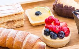 Wooden plate with small cakes. Wooden plate with the beautiful small cakes and mousses. Macro photography Stock Photography