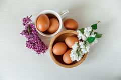 Wooden Plate and Ceramic Cup with Eggs,White and Purple Branches of Lilac.White Wooden Background.Top View Royalty Free Stock Images