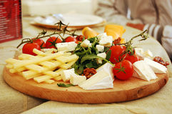 Wooden plate with cheese. And vegetables Royalty Free Stock Photography