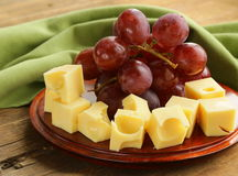 Wooden plate with cheese (Maasdam) and grapes Royalty Free Stock Images