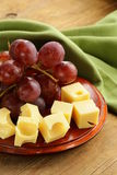 Wooden plate with cheese (Maasdam) and grapes Stock Photo