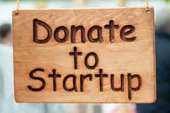 Wooden plate with Donate to Startup text Royalty Free Stock Photo