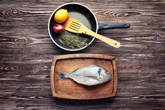 Wooden plate with fresh dorado fish and frying pan. On table Stock Photo