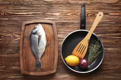 Wooden plate with fresh dorado fish and frying pan. On table Royalty Free Stock Photos