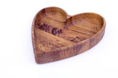 Wooden plate-heart isolated. Plate in the shape of heart close-up. Wooden heart on a white background royalty free stock photo