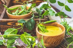 Wooden plate of pea soup and pods of fresh green peas on dark wooden surface royalty free stock photo
