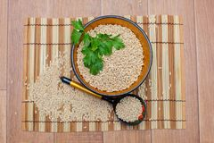 Wooden plate with pearl barley and parsley. The wooden plate with pearl barley decorated with parsley, Khokhloma Royalty Free Stock Photography