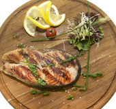 Wooden plate with a piece of fish Royalty Free Stock Images
