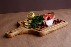 Wooden plate with salmon fish. Lemon and spices Royalty Free Stock Photography
