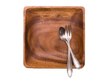 Wooden plate and silver utensils Stock Images