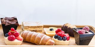 Wooden plate with small cakes. Wooden plate with the beautiful small cakes and mousses on the white background. Macro photography Royalty Free Stock Photo