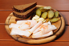 Wooden plate with smoked bacon, pickles and rye bread Stock Image