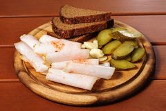 Wooden plate with smoked bacon, pickles and rye bread Royalty Free Stock Photos