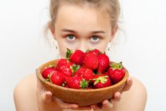 Wooden plate with strawberries in girl hand on light background royalty free stock photo