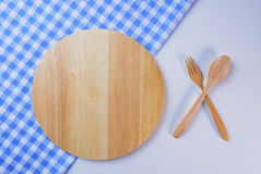 Wooden plate, tablecloth, spoon, fork on table Stock Images