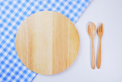 Wooden plate, tablecloth, spoon, fork on table Stock Image