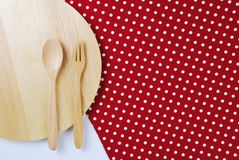 Wooden plate, tablecloth, spoon, fork on table Royalty Free Stock Photos