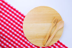 Wooden plate, tablecloth, spoon, fork on table Royalty Free Stock Image