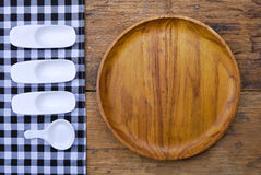 Wooden plate, tablecloth, spoon, fork on  table background Stock Image