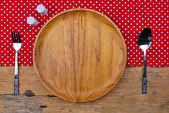 Wooden plate, tablecloth, spoon, fork on  table background Stock Images