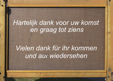 Wooden plate with thank you fror coming in dutch en german Stock Images