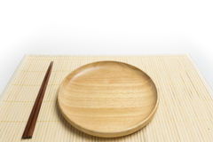 Wooden plate or tray with chopsticks place on a bamboo mat isolated white background Royalty Free Stock Photography