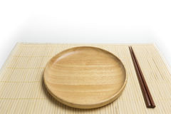 Wooden plate or tray with chopsticks place on a bamboo mat isolated white background Stock Photography