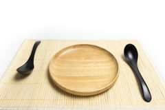 Wooden plate or tray with spoon place on a bamboo mat white background Stock Photo