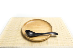 Wooden plate or tray with spoon place on a bamboo mat white background Stock Photos