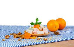 A wooden plate of Turkish delight or lokum, walnuts, dried apricots and sappy oranges  on a white background. A wooden table with two juicy oranges, a plate of Stock Images