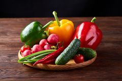 Wooden plate with vegetables for a vegetarian salad on rustic wooden background, close-up, selective focus. Cucumber, raddish, bell pepper and hot pepper ready stock photography