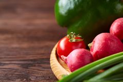 Wooden plate with vegetables for a vegetarian salad on rustic wooden background, close-up, selective focus. Cucumber, raddish, bell pepper and hot pepper ready royalty free stock photos