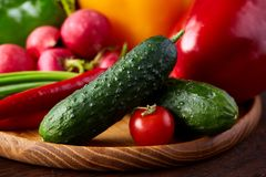 Wooden plate with vegetables for a vegetarian salad on rustic wooden background, close-up, selective focus. Cucumber, raddish, bell pepper and hot pepper ready royalty free stock photography
