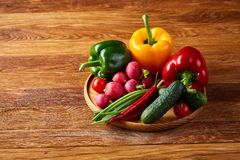 Wooden plate with vegetables for a vegetarian salad on rustic wooden background, close-up, selective focus. Cucumber, raddish, bell pepper and hot pepper ready royalty free stock image