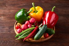 Wooden plate with vegetables for a vegetarian salad on rustic wooden background, close-up, selective focus. Cucumber, raddish, bell pepper and hot pepper ready stock photo