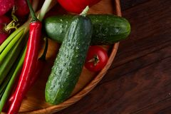Wooden plate with vegetables for a vegetarian salad on rustic wooden background, close-up, selective focus. Cucumber, tomatoes and hot pepper ready to eat stock image