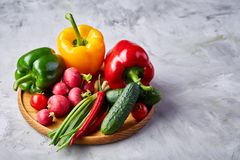 Wooden plate with vegetables for a vegetarian salad on white textured background, close-up, selective focus. Cucumber, raddish, bell pepper and hot pepper with stock photography