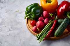 Wooden plate with vegetables for a vegetarian salad on white textured background, close-up, selective focus. Cucumber, raddish, bell pepper and hot pepper with stock photo