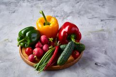 Wooden plate with vegetables for a vegetarian salad on white textured background, close-up, selective focus. Cucumber, raddish, bell pepper and hot pepper with royalty free stock photo