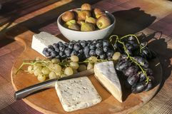 Wooden plateau with grapes and cheese Royalty Free Stock Photo