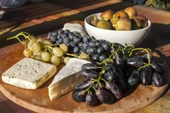 Wooden plateau with grapes and cheese Royalty Free Stock Images
